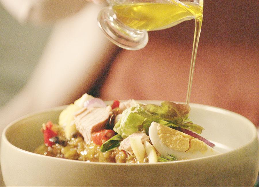 Gesund und lecker mit Olivenöl kochen. Olivenöl über Salat giessen