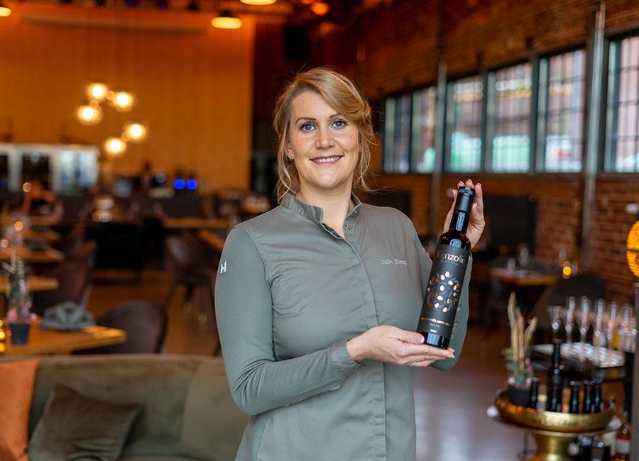 Julia Komp hält Flasche Olivenöl nativ extra von Kenzolie in der Hand