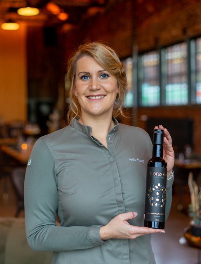 Sterneköchin Julia Komp trägt eine Bio Olivenöl Flasche Kenzolie