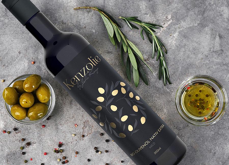 Olivenöl in einer schützenden Flasche aus Violettglas neben Oliven und Olivenzweigen